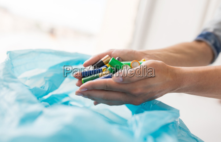 close up of hands putting batteries