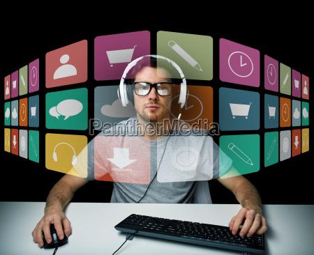 hombre en auriculares con ordenador e