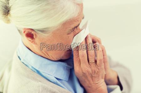 enfermo senior mujer soplando nariz a