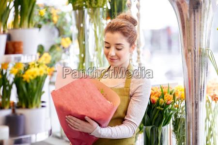 mujer florista sonriente con racimo en