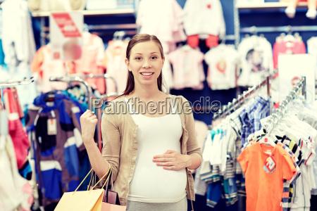 mujer embarazada feliz comprando en la