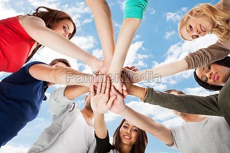 jovenes estudiantes universitarios de apilamiento manos