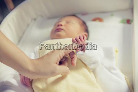 hand of newborn baby holding finger