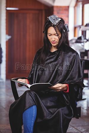 mujer leyendo una revista mientras espera