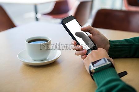 mano con telefono movil con taza