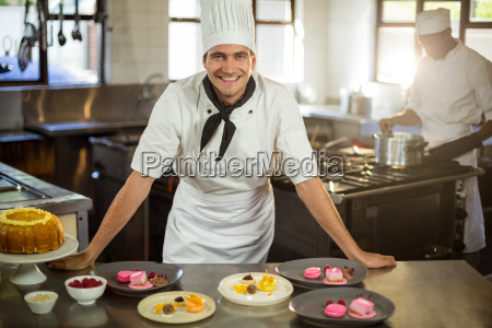 retrato de chef sonriente presentando platos