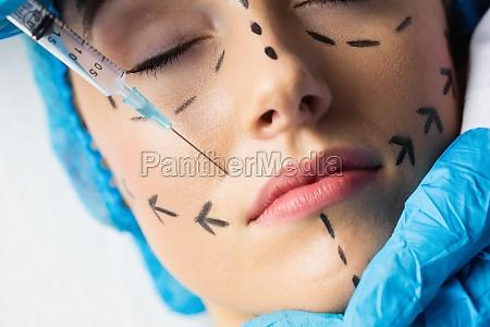 mujer recibiendo botox inyectable en sus