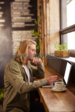 young man using laptop in cafeteria