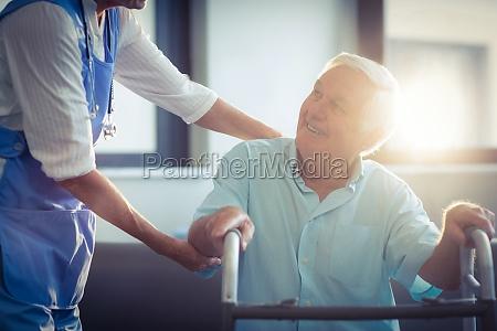 doctora ayudar a hombre mayor a