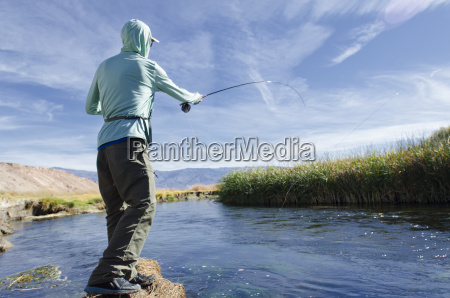 a young man fly fishes on