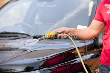 man with hose spraying washing car