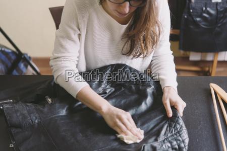 mujer limpiando chaqueta de cuero