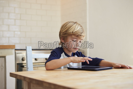 young boy using tablet computer at