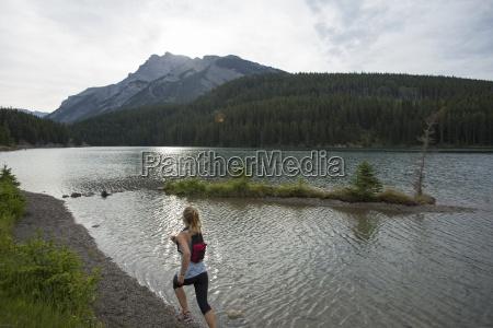 young woman runs along edge of