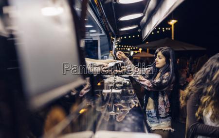 mujer joven que toma la comida
