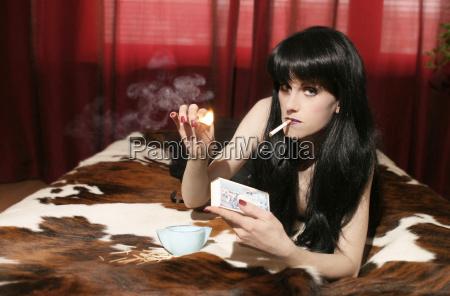 woman lying on bed smoking cigaret