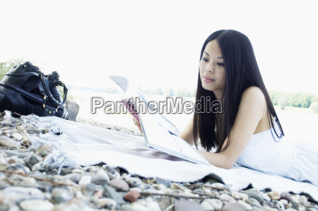germany young woman lying and reading