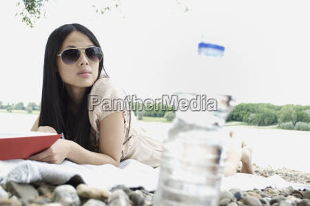 germany young woman lying with book
