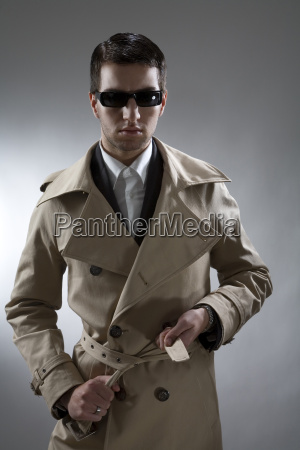 young man wearing trenchcoat and sunglasses