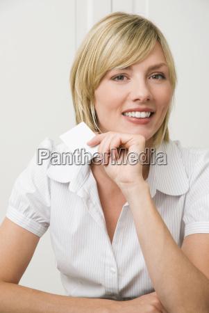 mujer joven tenencia tarjeta de visita