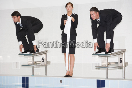 businessmen crouching on starting blocks woman