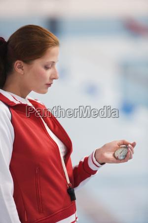 mujer joven sosteniendo el reloj de