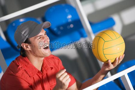 young man wearing cap holding ball