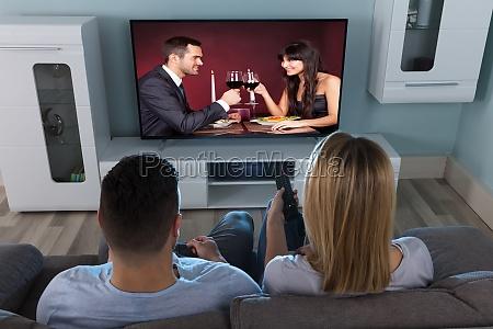 pareja viendo television en casa