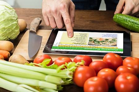 person is preparing recipe using digital