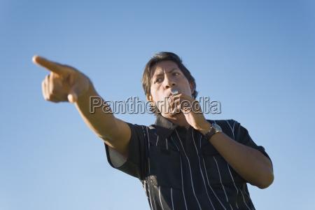 Arbitro de futbol silbando