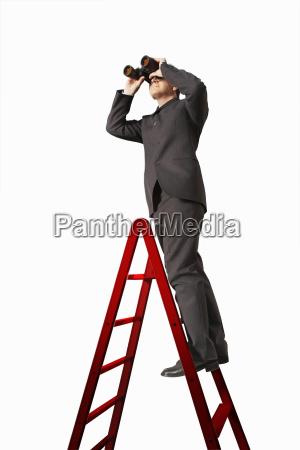 empresario en escalera mirando a traves