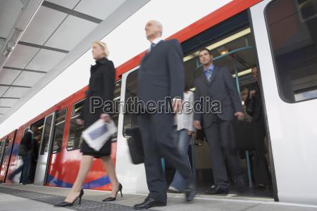 viajeros de negocios bajarse del tren