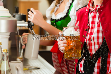 young woman drawing beer in restaurant
