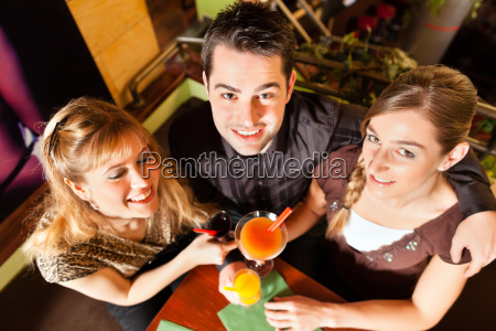 young people drinking cocktails in bar