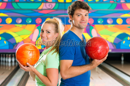 young people playing bowling and having