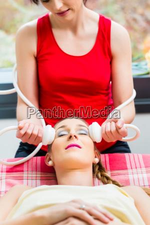 woman having face massage in wellness