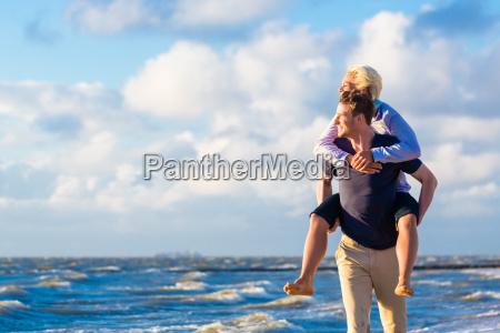 man carrying woman piggyback at beach