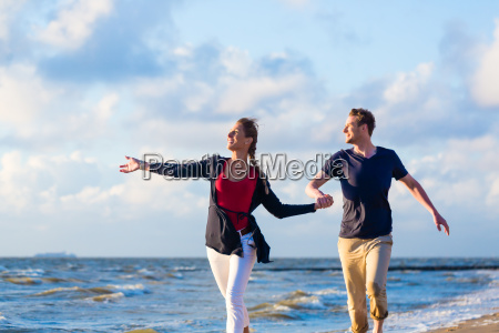 couple running through sand and waves