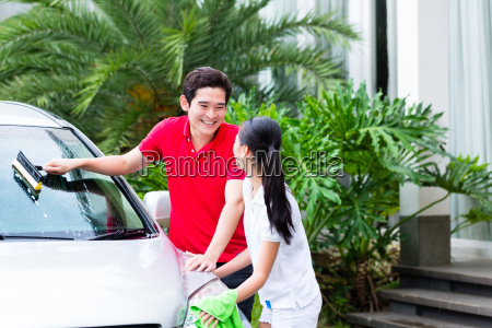 asian couple cleaning together car