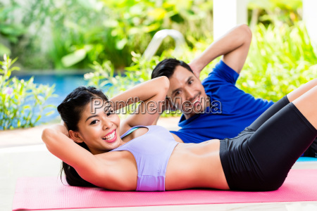 asian fitness couple doing sit up