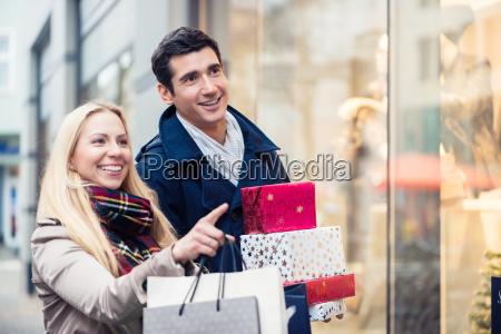 pareja en el escaparate haciendo compras