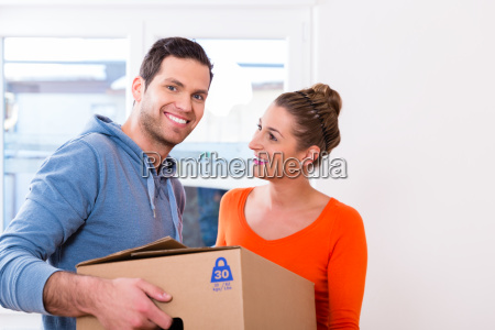 couple moving house carrying packing cases