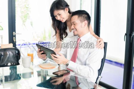 couple having breakfast before man goes