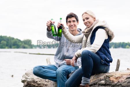 couple sitting on tree stump at