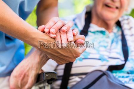 enfermera consolando senior mujer sosteniendo su
