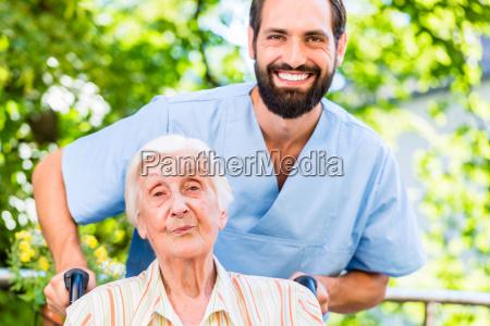 enfermera geriatrica empujando a la senyora