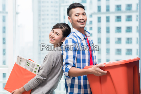 young indonesian couple carrying moving boxes
