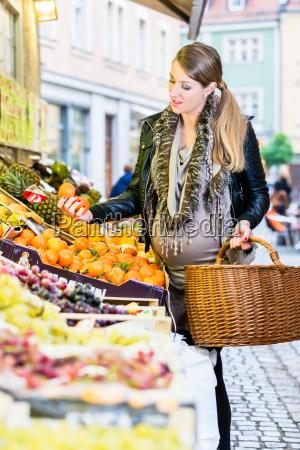 mujer embarazada comprando comestibles en el