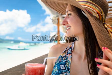 woman in beachwear enjoying drink in