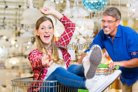 man pushing woman in shopping cart